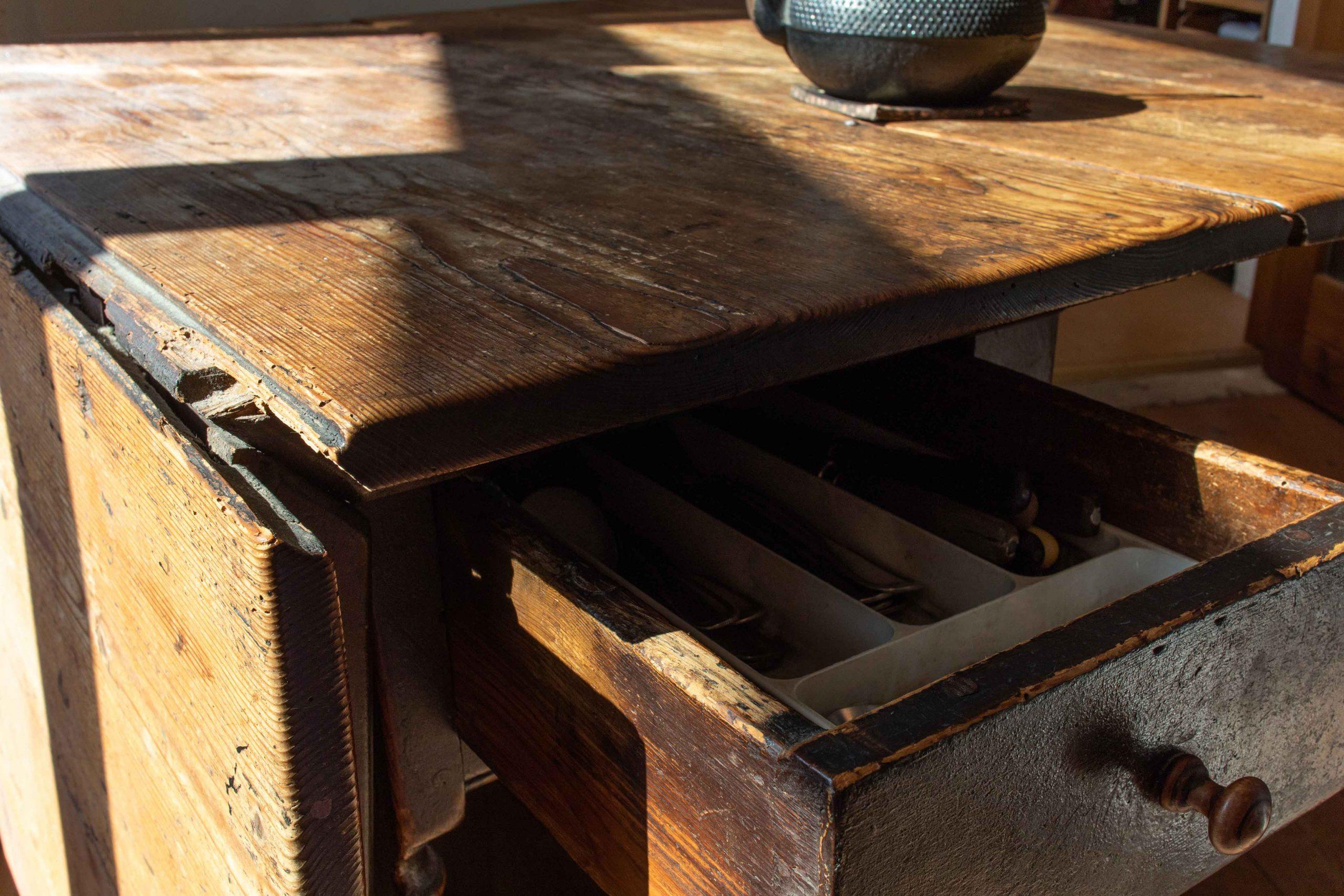 alter guter Tisch, Holzplatte und offene Besteckschublade