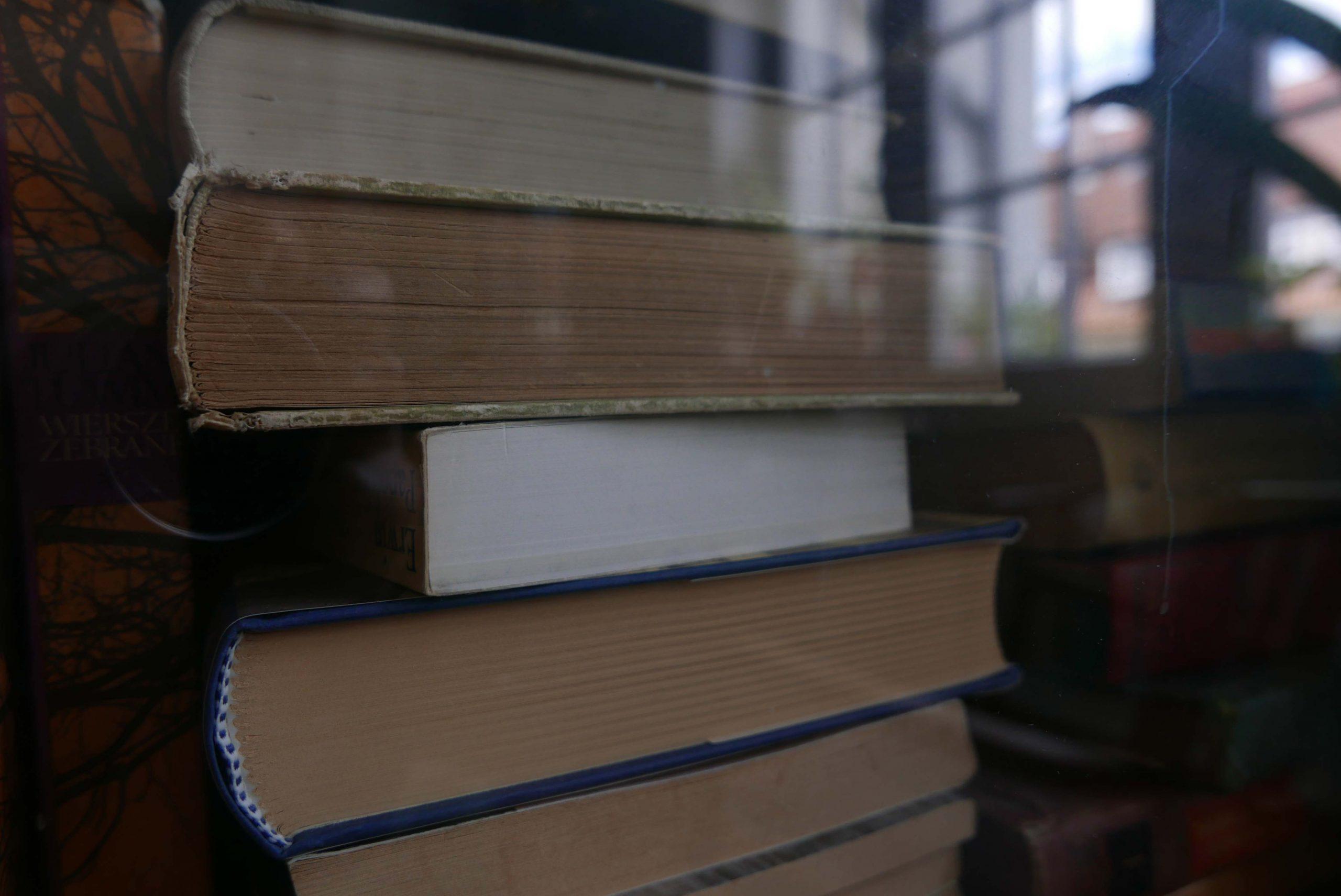 Bücher in dem Bücherschrank mit Spiegelung eines Fensters