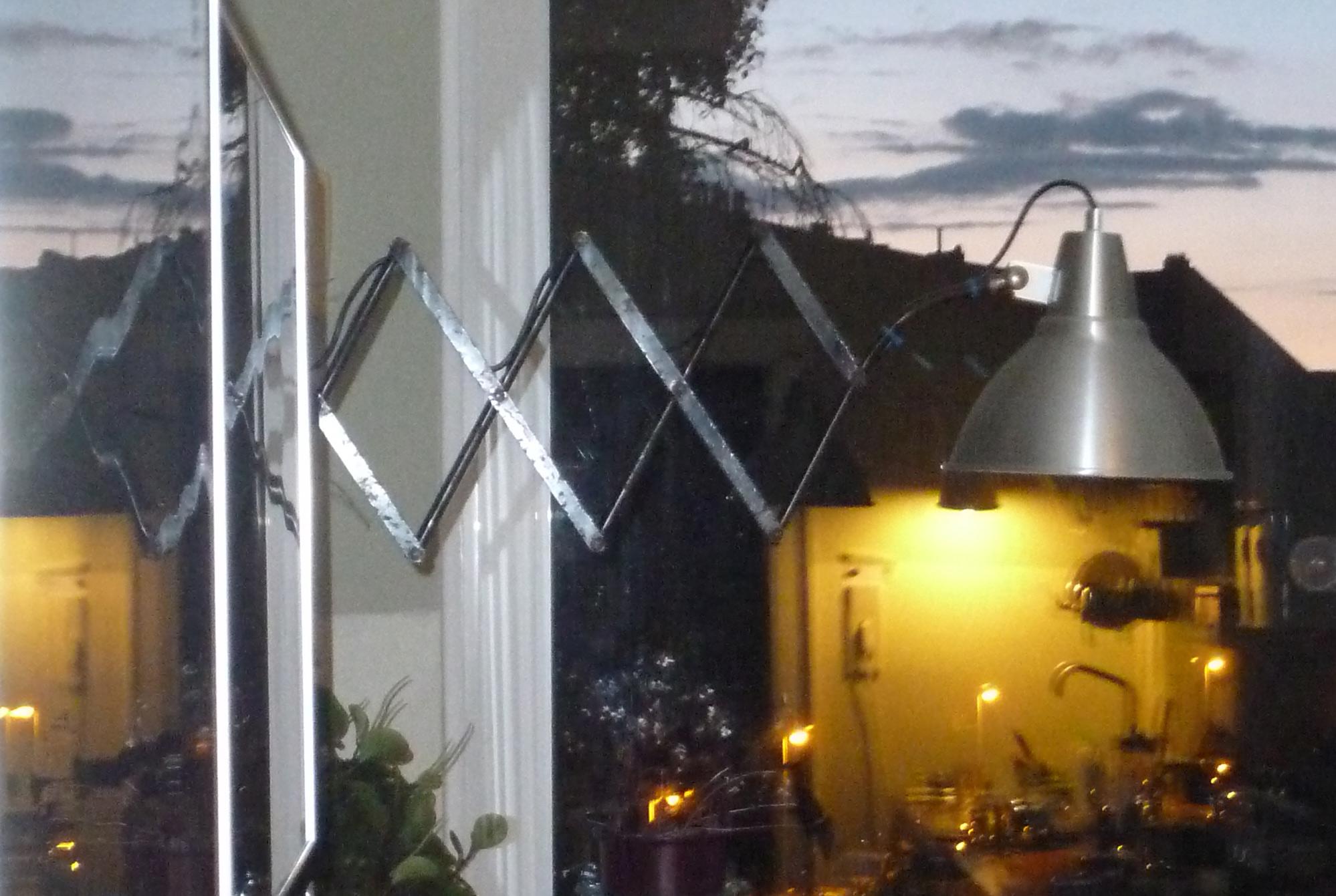 Abendliche Spiegelung einer Scherenlampe in den Küchenschränken