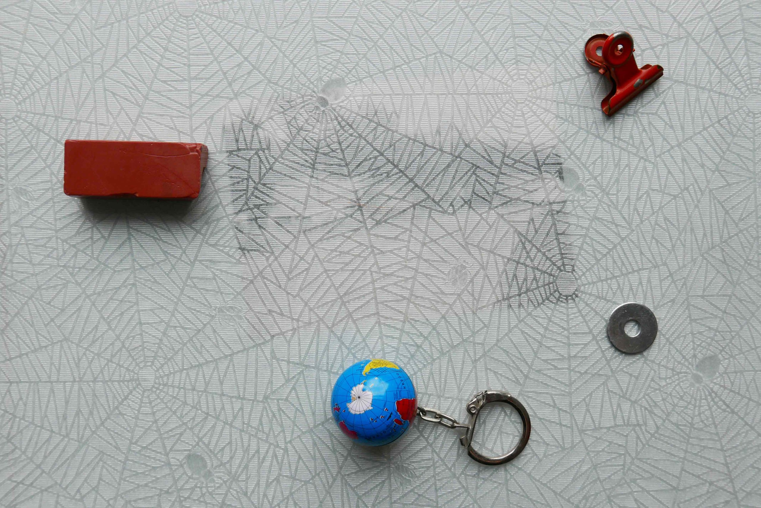 Seidenpapier mit Fotografie darunter und kleine Gegenstände verteilt