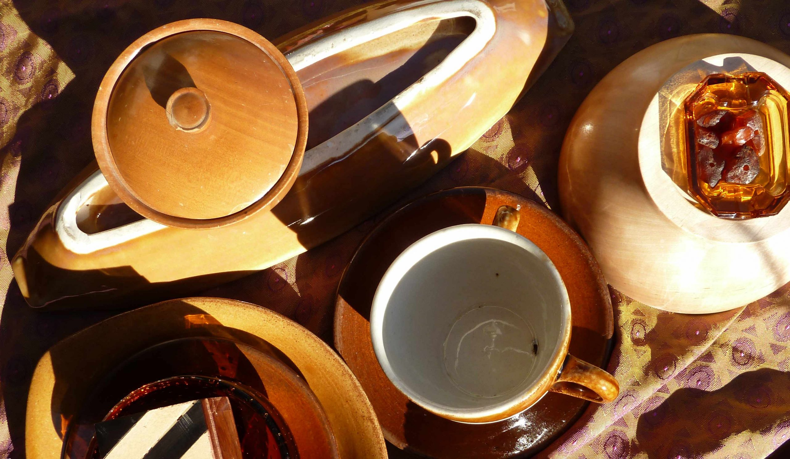 Bernsteinfarbene Keramik und Glasgefäße in der Sonne