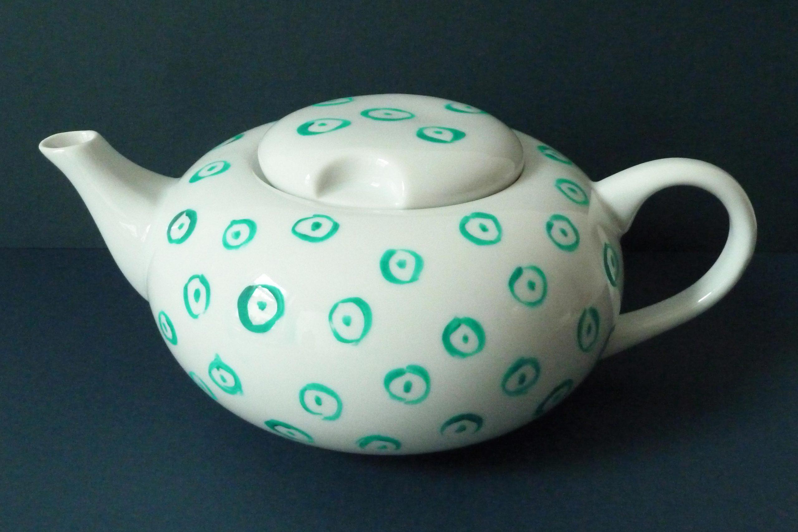 Weiße Teekanne mit einem kleinteiligen Krawattenmuster in Grün
