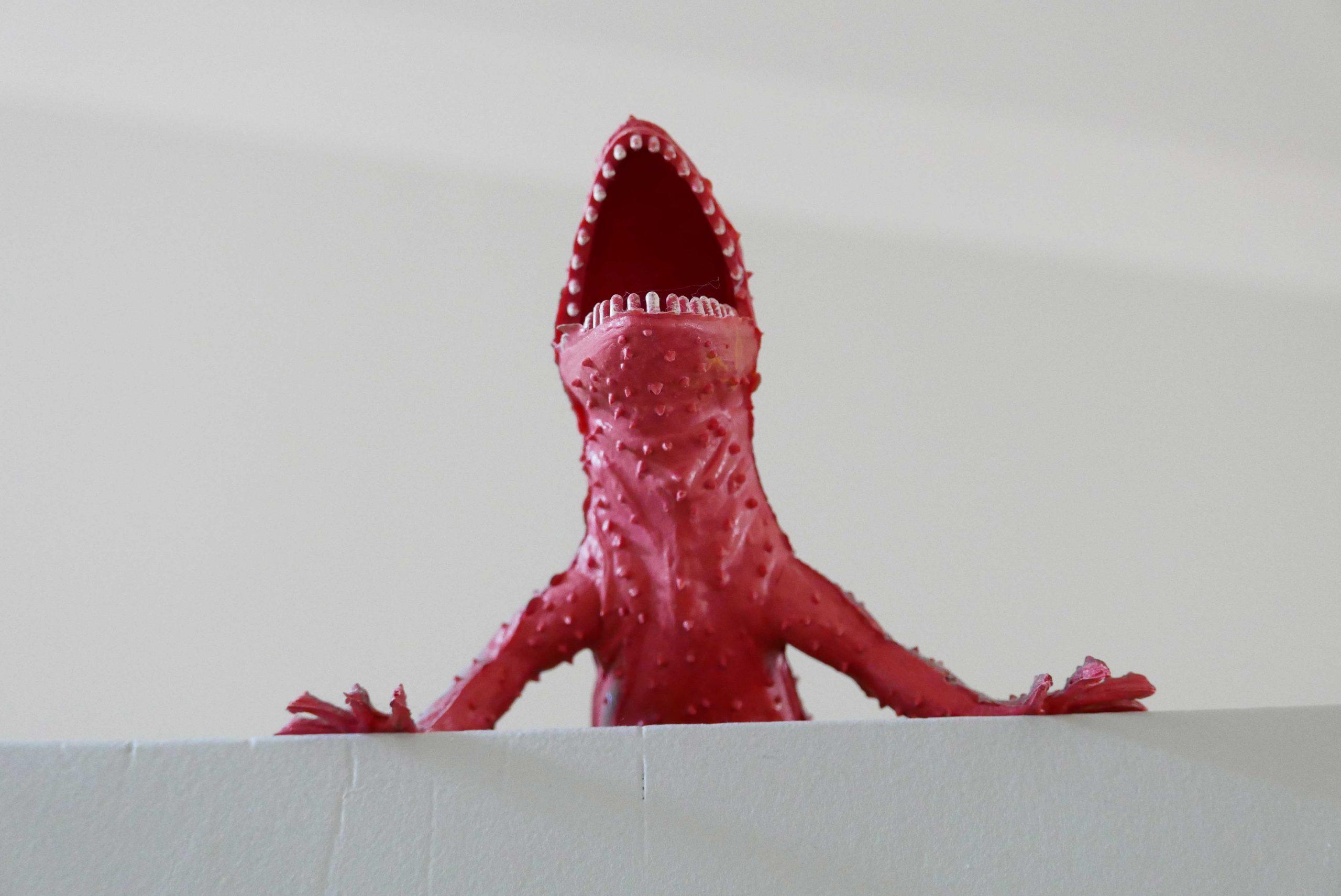 Roter Drache Dino auf einem grauen Schrank