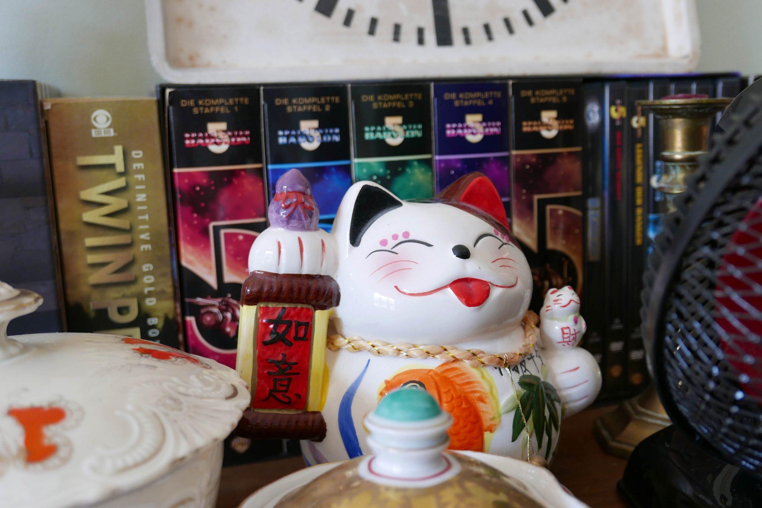 Glückskatze aus Keramik mit DVD Babylon 5 und Twin Peaks im Hintergrund