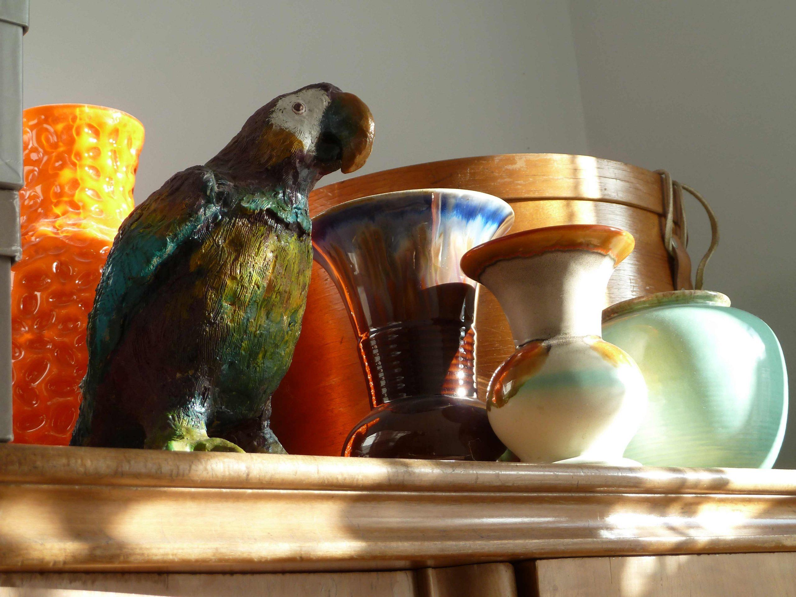 Figur Papagei auf dem Schrank zwischen Vasen