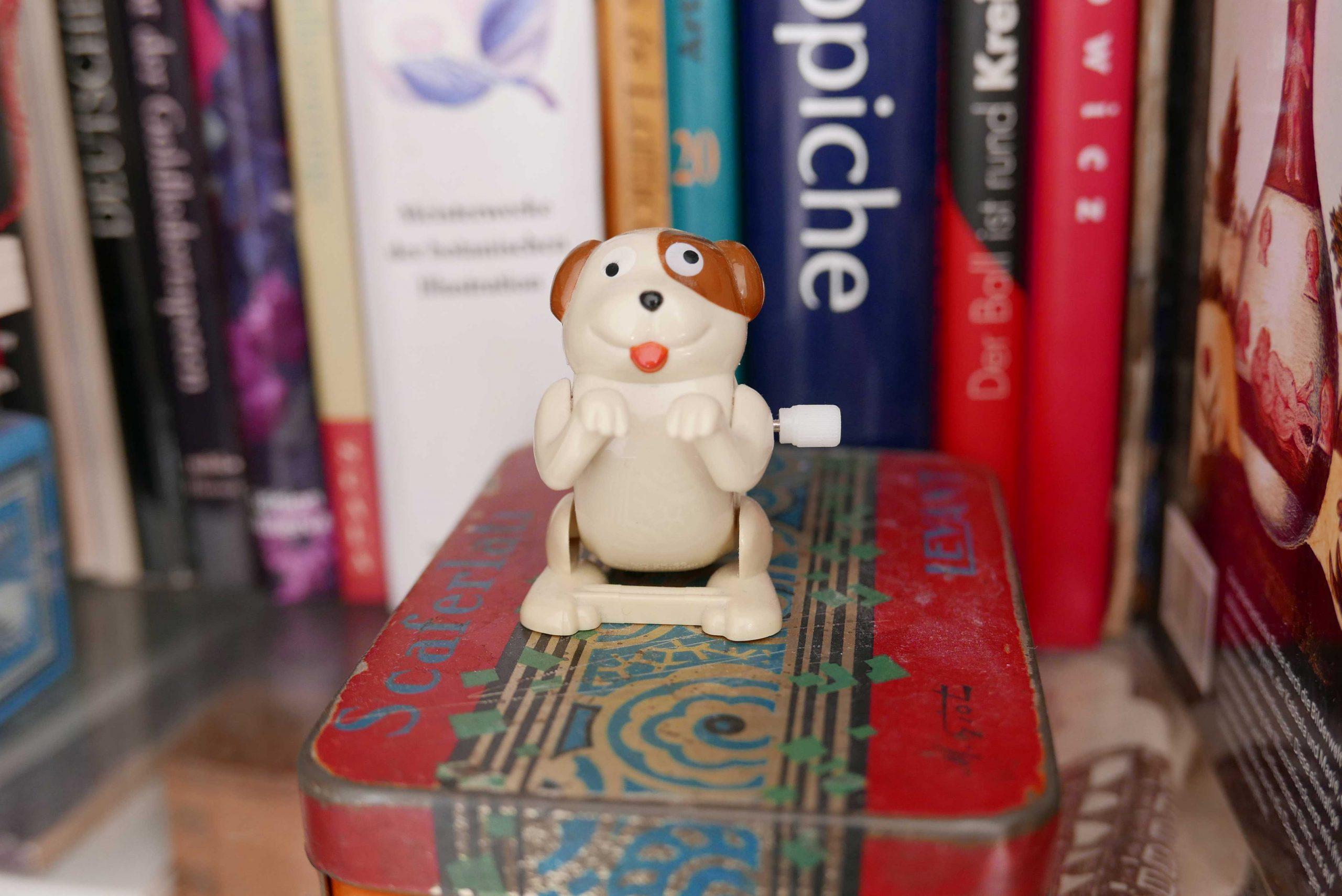 Plastikhund zum Aufziehen im Bücherregal
