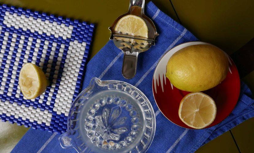 Zitronen und Zitronenpressen auf dem Tisch mit blauem Tuch und Perlendeckchen