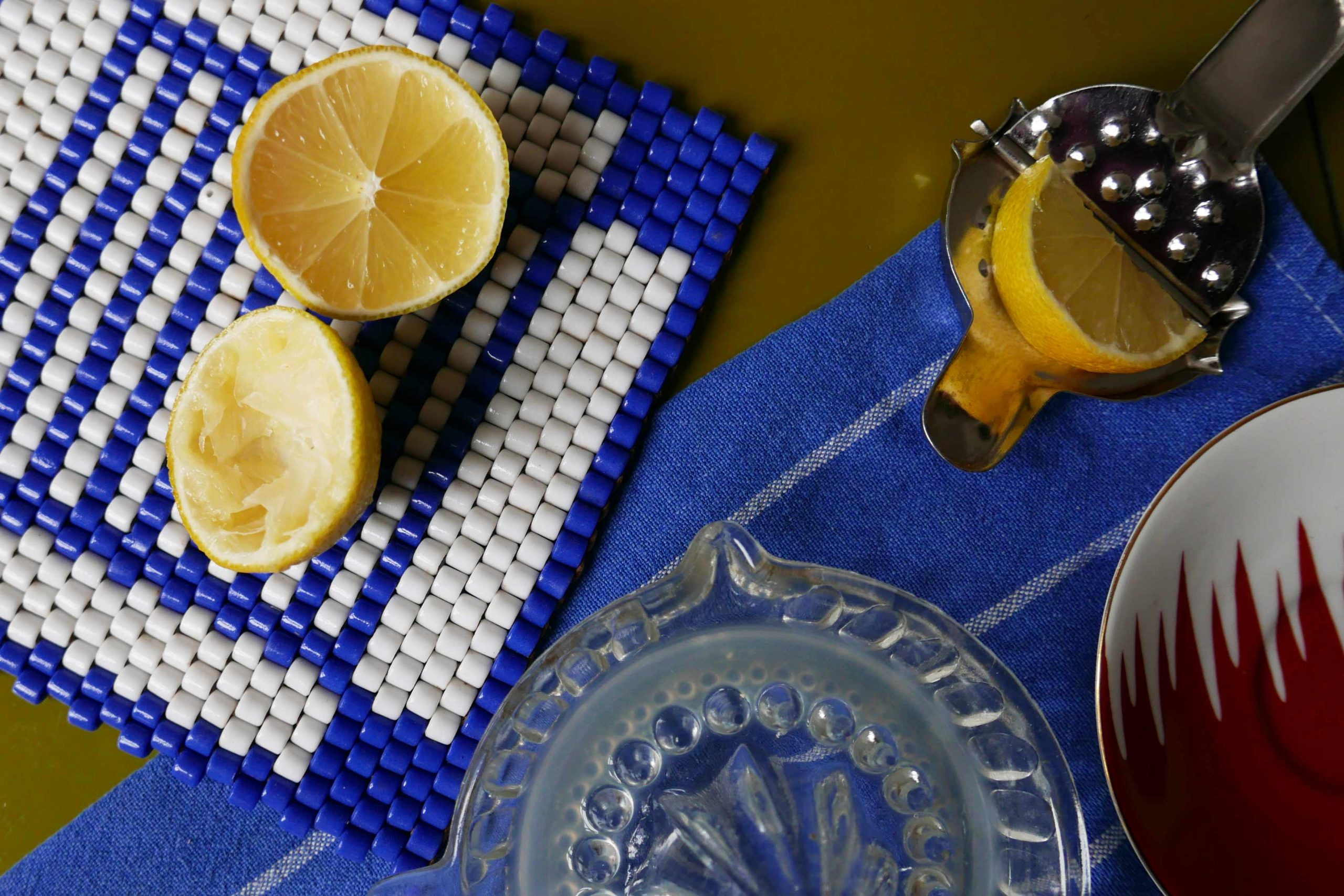 Arbeitsplatte in der Küche mit Zitronen und verschiedenen Zitronenpressen auf blauem Tuch