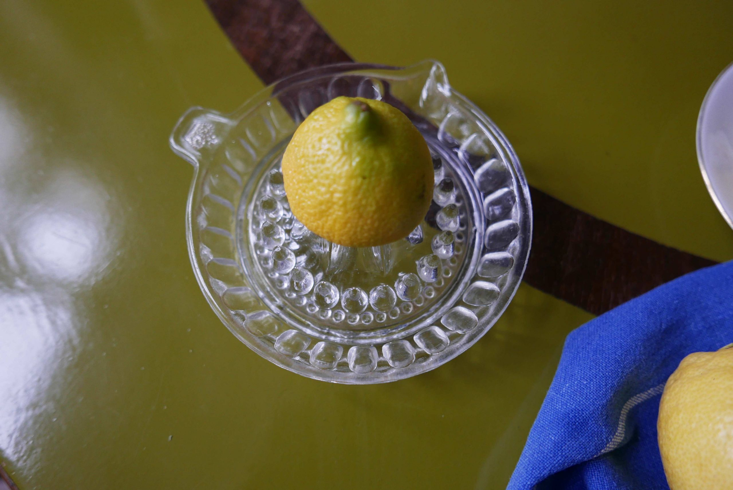 Vintage Zitronenpresse aus Glas mit einer halben Zitrone