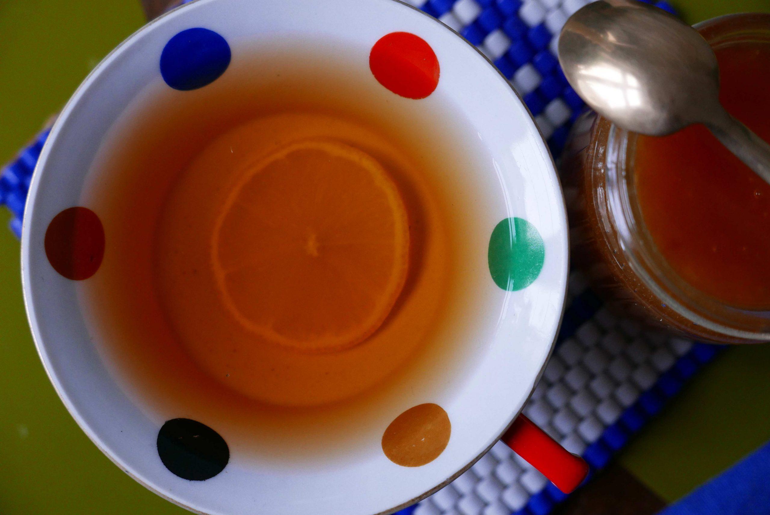 Tee mit einer Zitronenscheibe und Honigglas mit goldenem Löffel