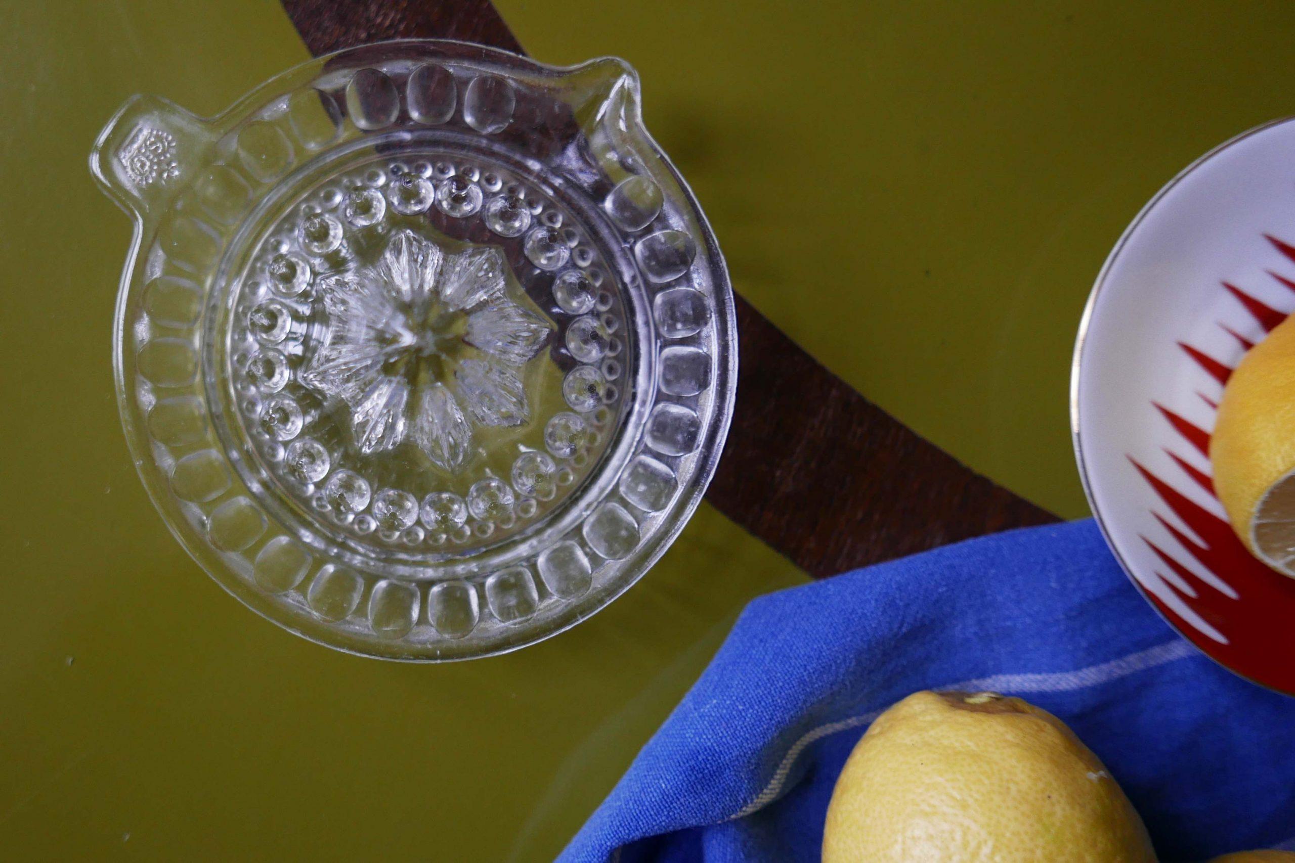 Vintage Zitronenpresse aus Glas auf einem grünen Tisch