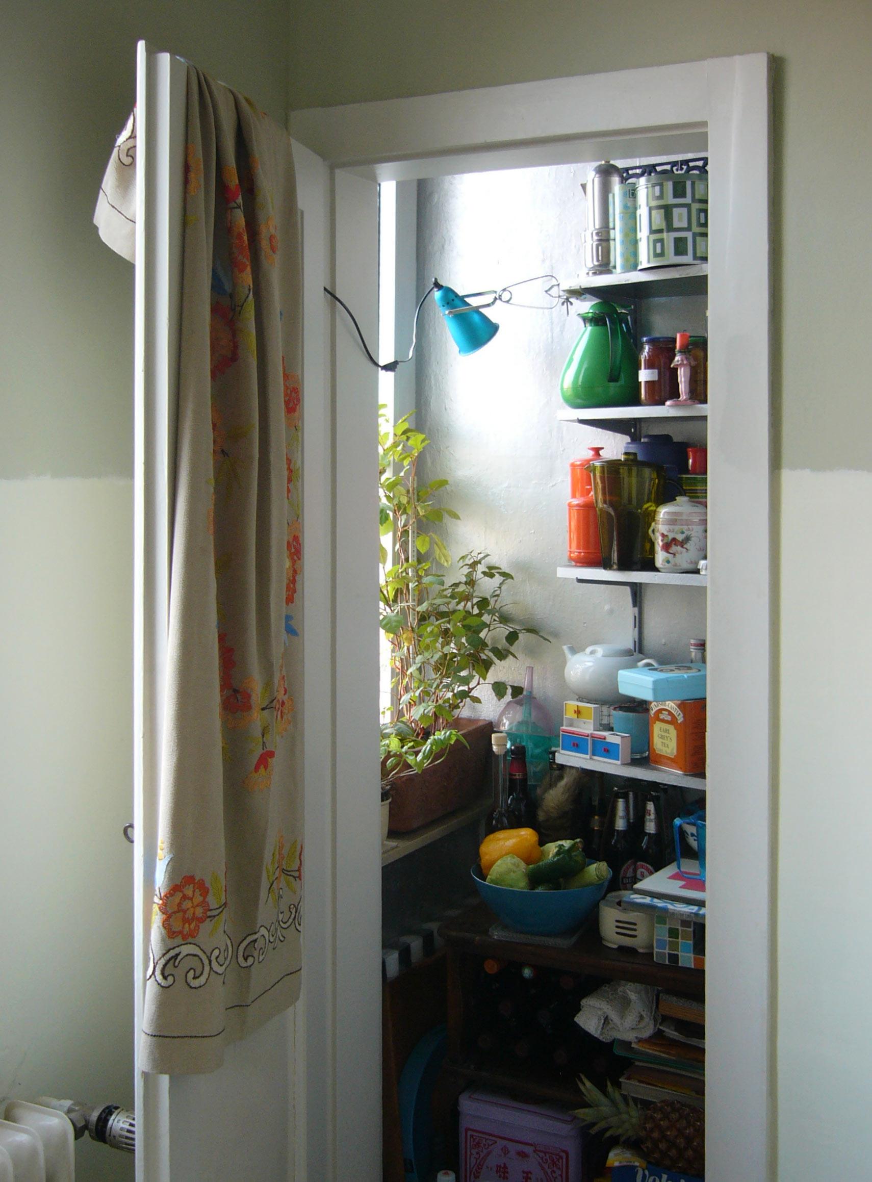Offene kleine Tür führt zur Speisekammer mit vielen Regalen