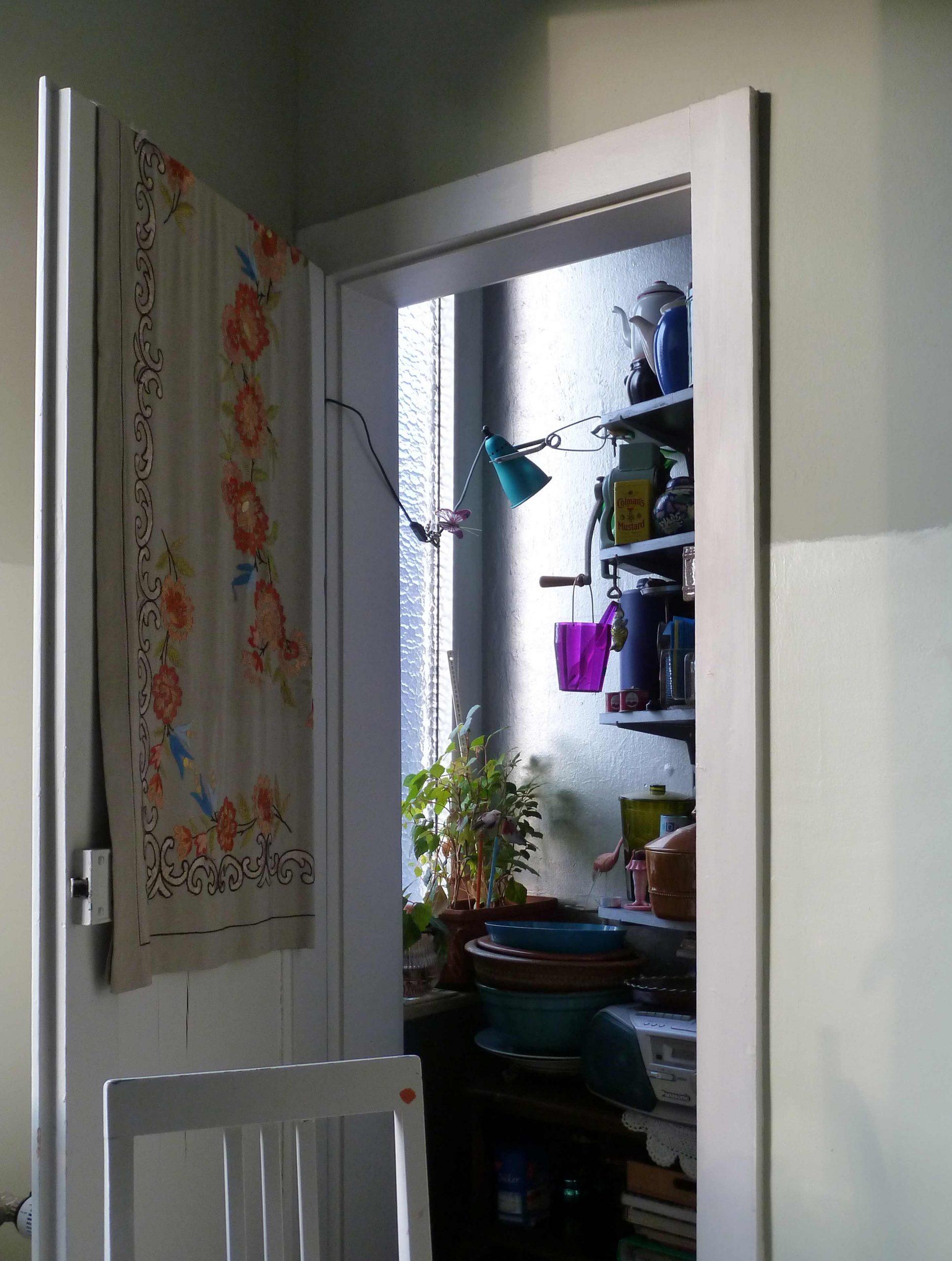 Offene kleine Tür zur Speisekammer, vorne ein Stuhl