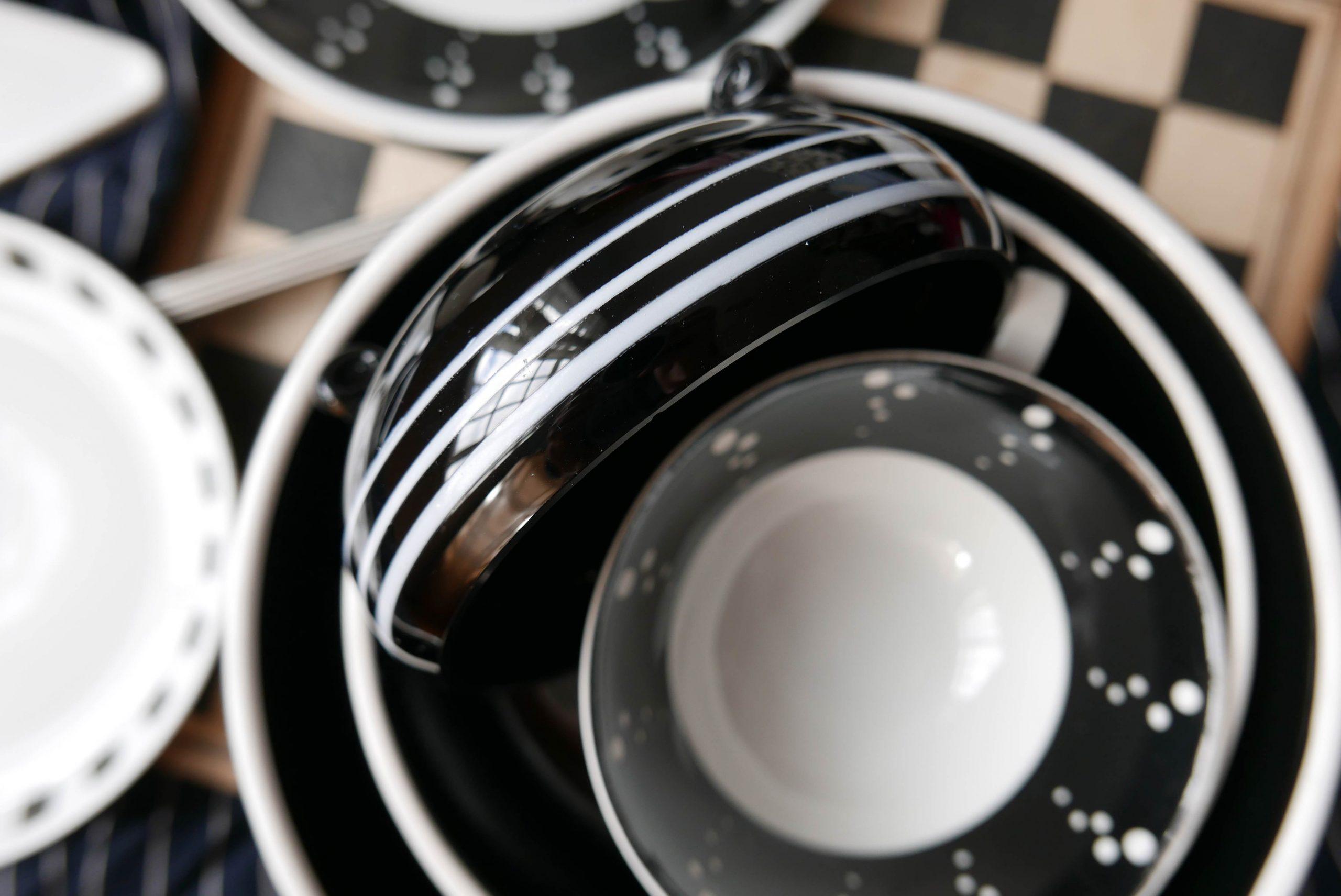 Komposition der Schwarzen und weissen Porzellangefässe auf einem Schachbrett