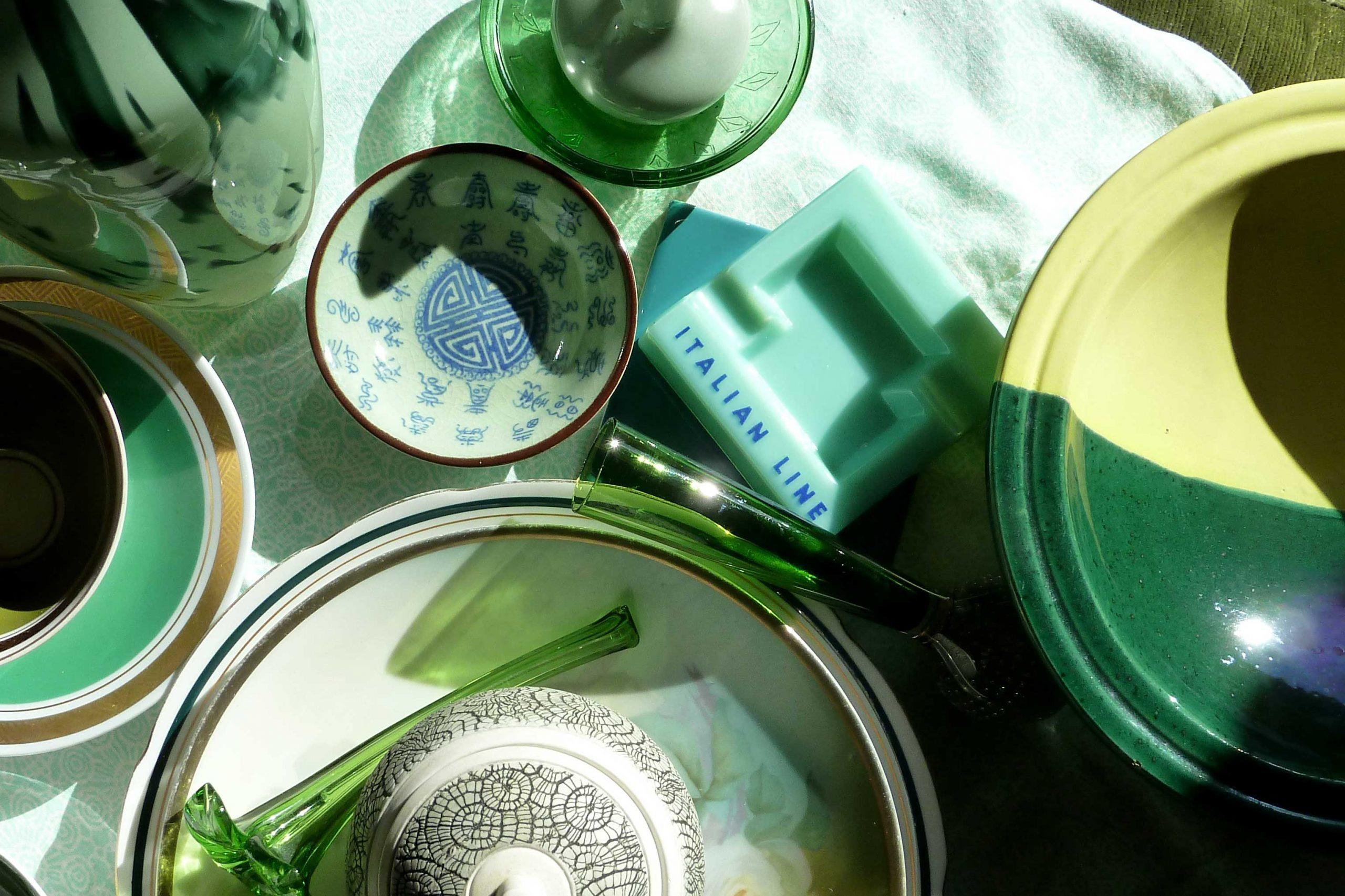 Gegenstände aus grünem GLas und Pporzellan in der Sonne in Mai