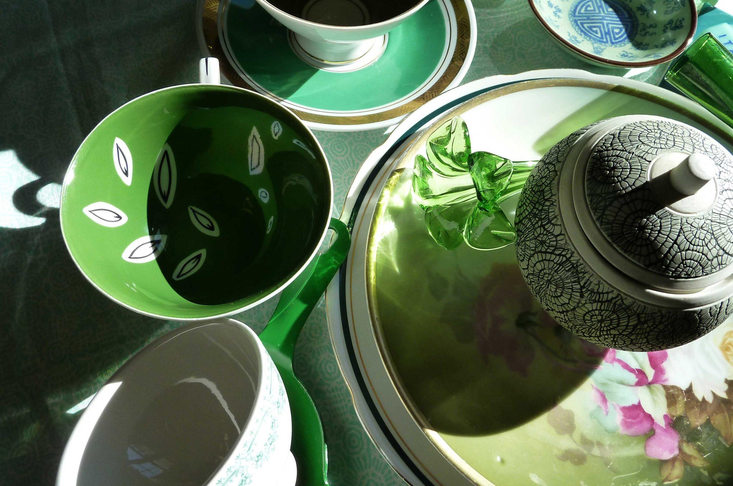 Grünes Glas und Porzellan in starken Licht Schatten Kontrasten
