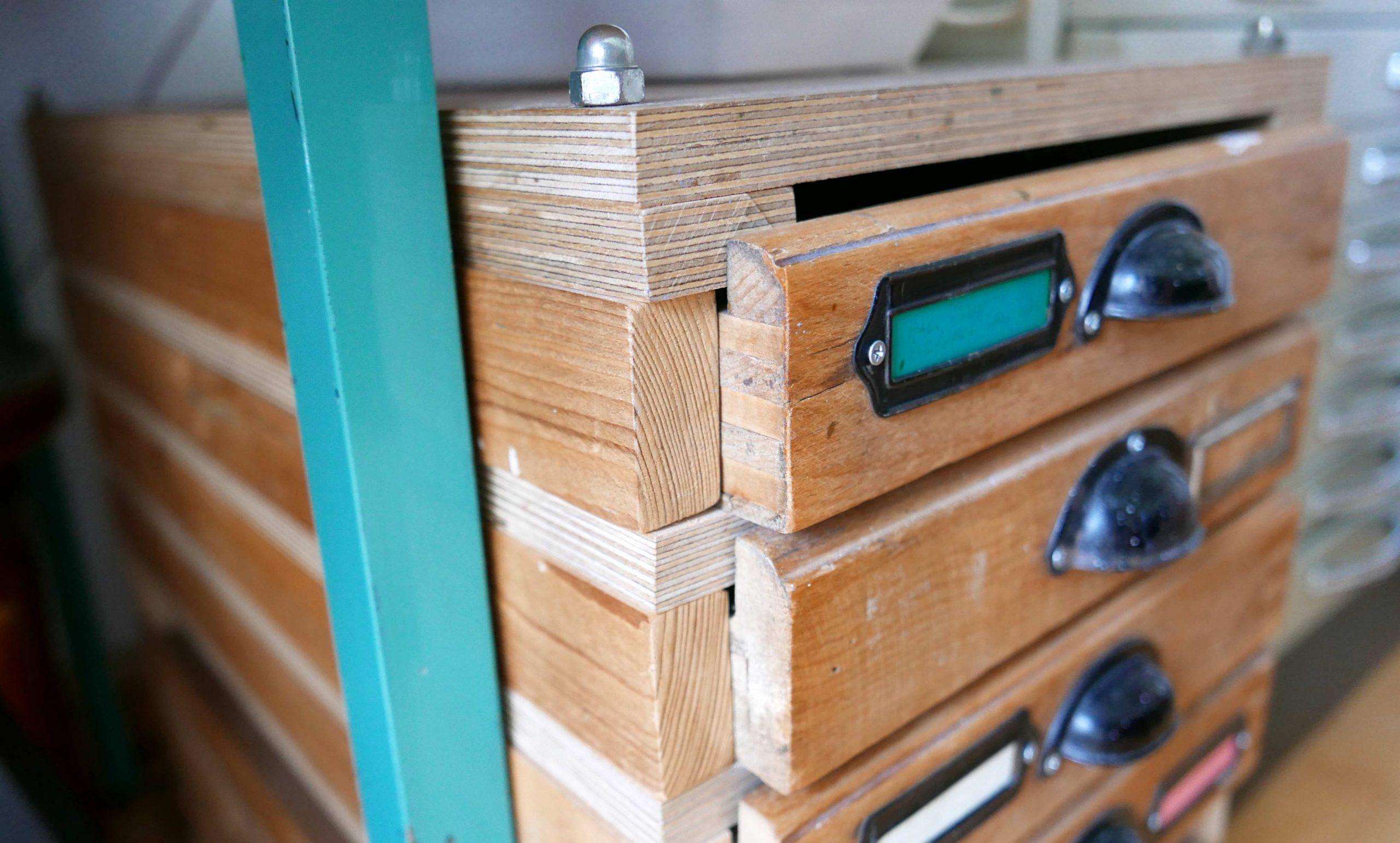 Detail eines Schranks mit Bleisatzschubladen Gewindestangen und Sperrholz