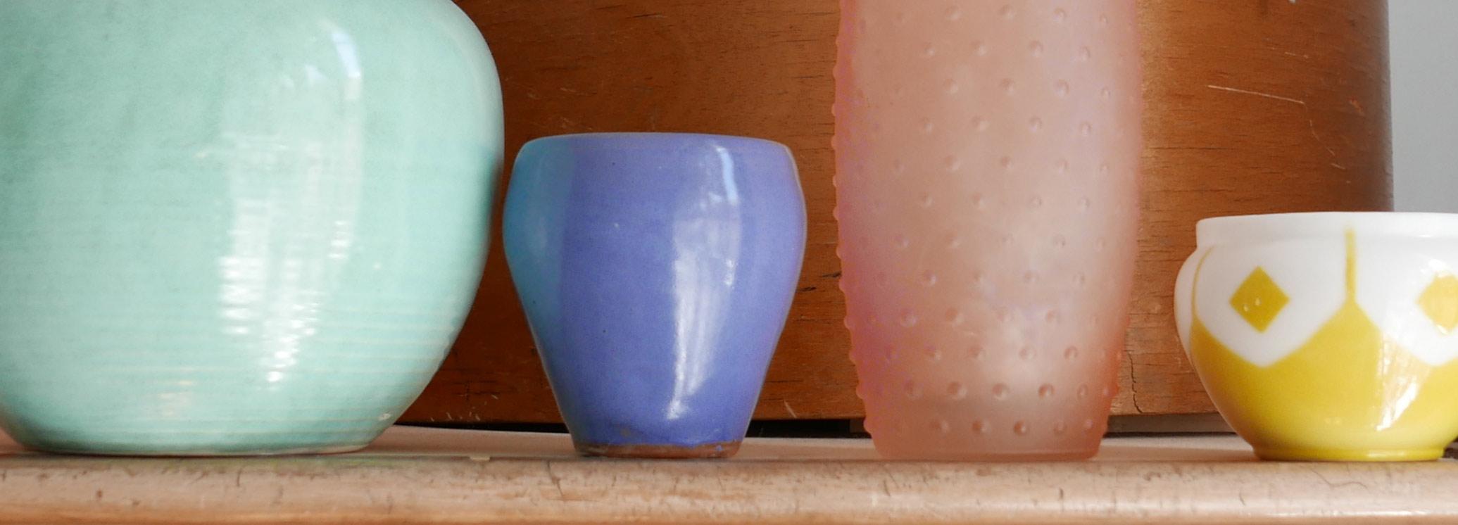 Pastellfarbene Blumenvasen in einer Reihe