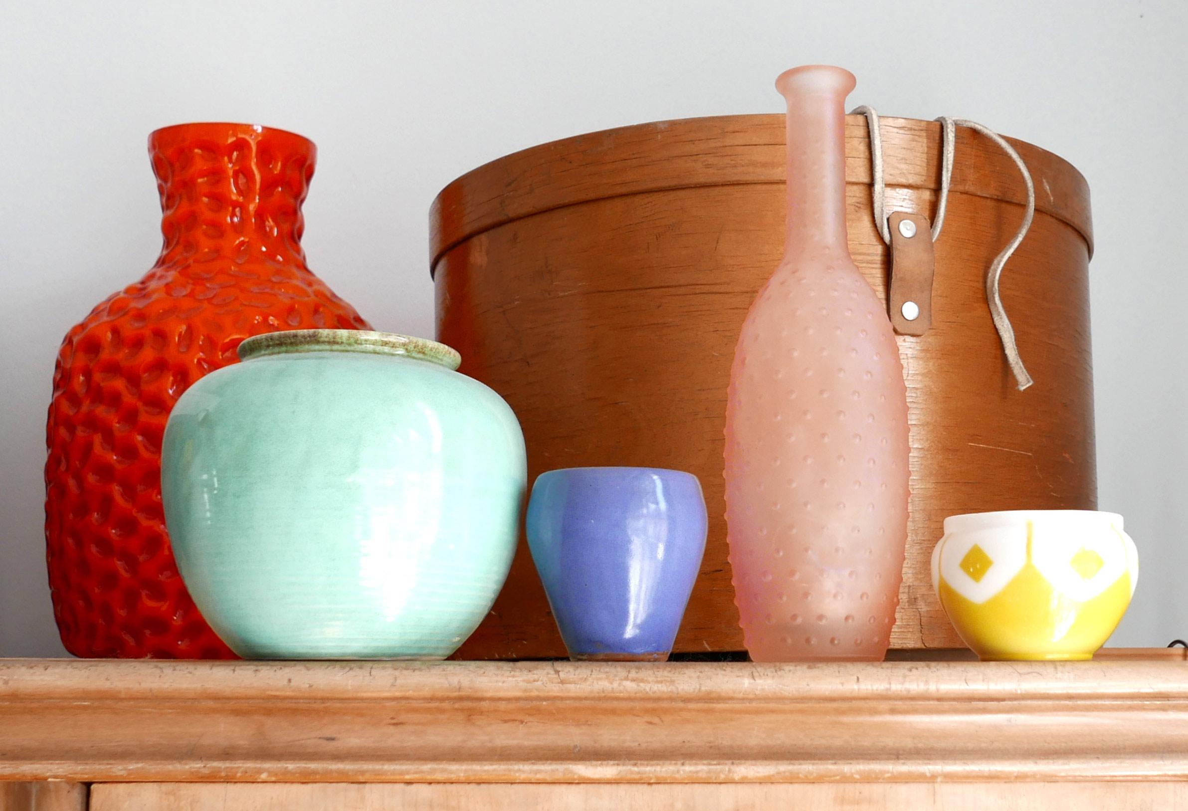 Pastellfarbene Blumenvasen auf einem Schrank dahinter Shaker Holzschachtel
