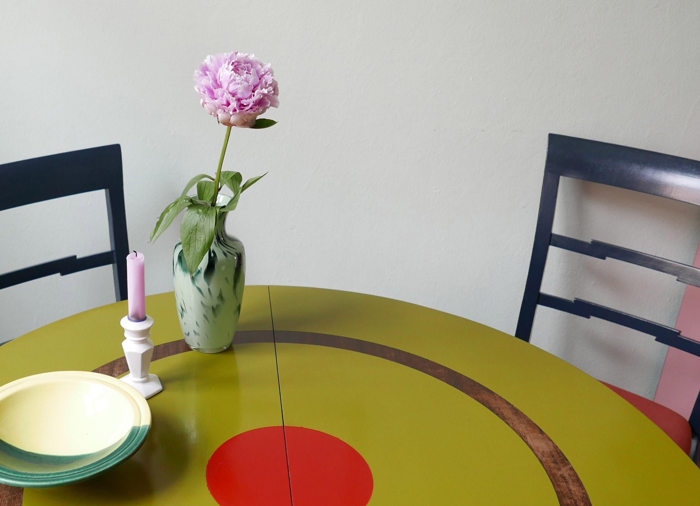 Grüner Tisch mit einer Pfingstrose in einer grünen Vase