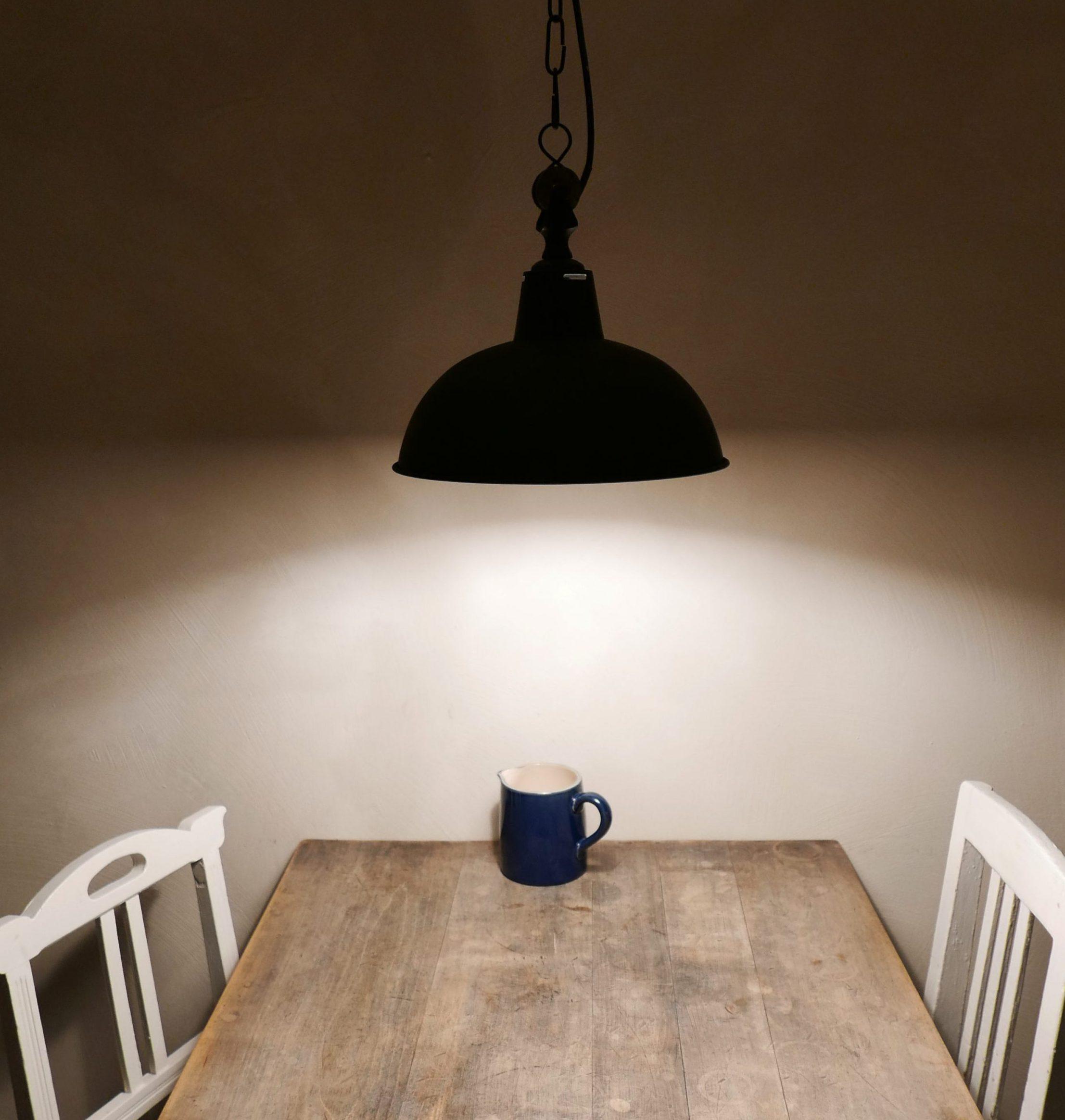 Holztisch in der Pension Elbeglück zwei alte weiße Stühle unter der Lampe