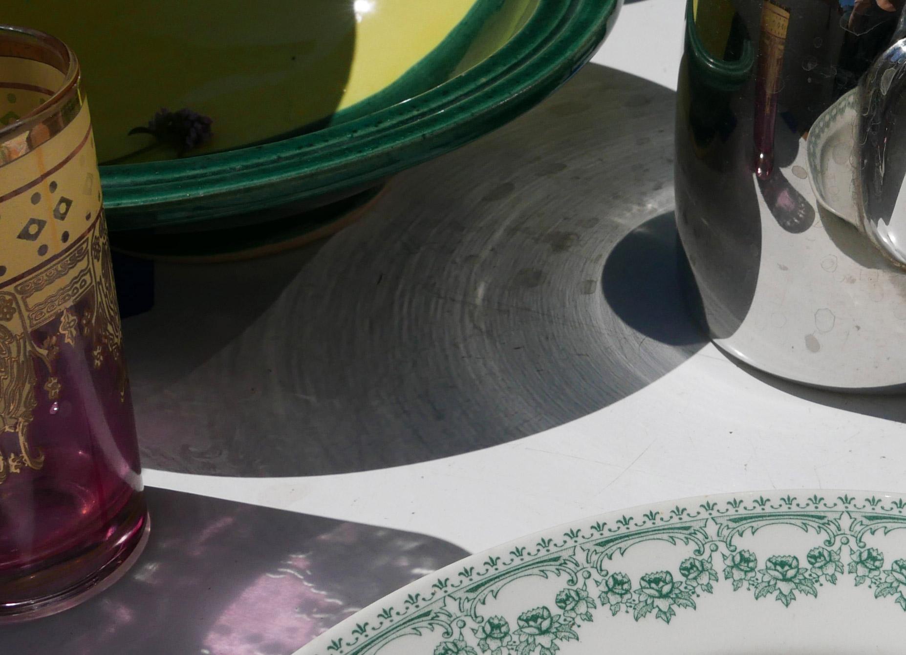 Schatten und Spiegelungen zwischen Gläsern, Edelstahlkanne in der vollen Sonne