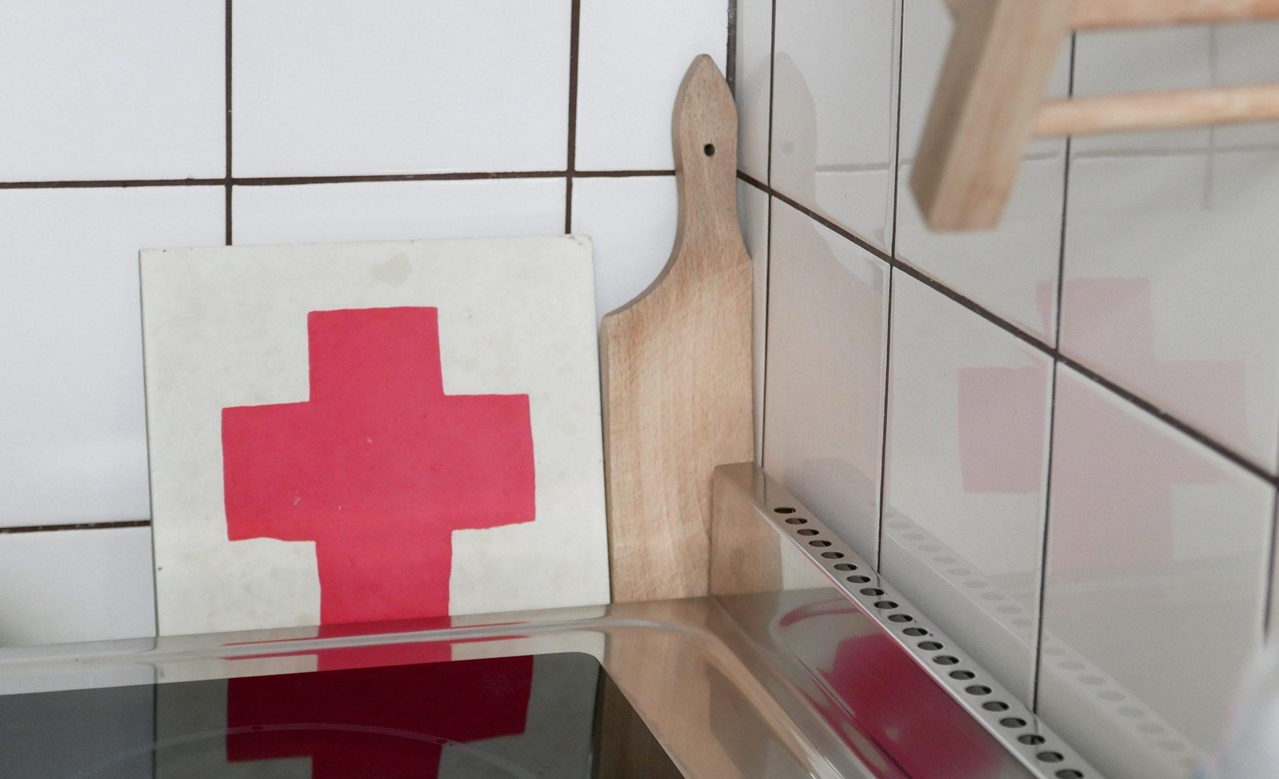 Spiegelung einer Zementfliese mit einem roten Kreuz